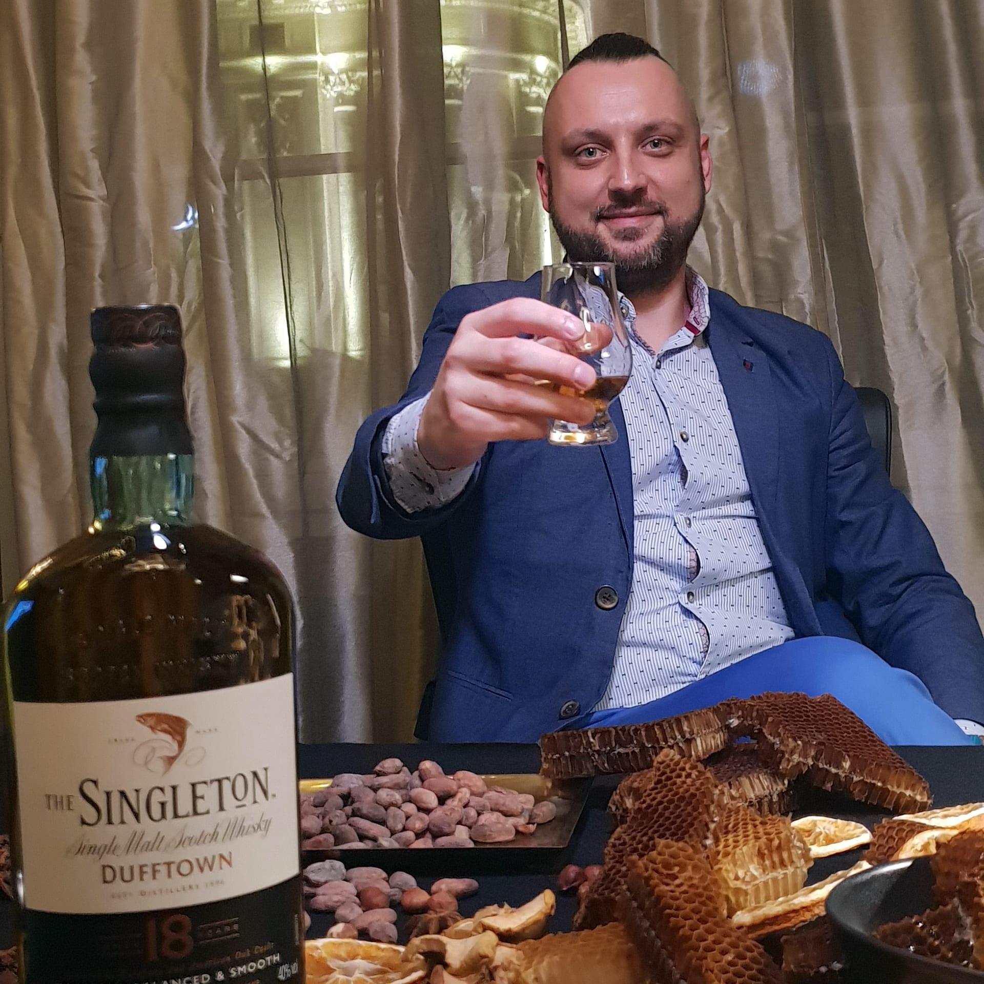 Whisky Singleton - toast wznoszony przez mężczyznę w ciepłym nastroju